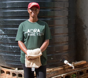 ADRA Jamaica workers stands by water storage tank