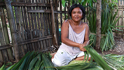 Woman in Philippines makes Shingles out of Nipa Leaves