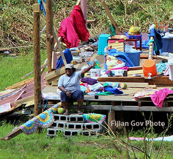 Victim of Cyclone Winston sits on corner of what is left of her house