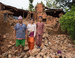 Father and Daughter stand by fallen house in Nepal