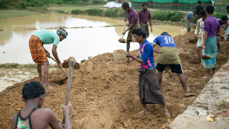 Rohingya men work to improve the water flow in their camp.